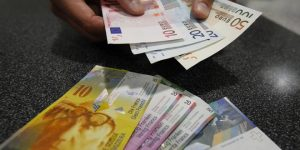 A illustration picture shows a Swiss Post clerk as he exchanges Swiss francs into Euros at a counter in a Swiss Post office in Bern